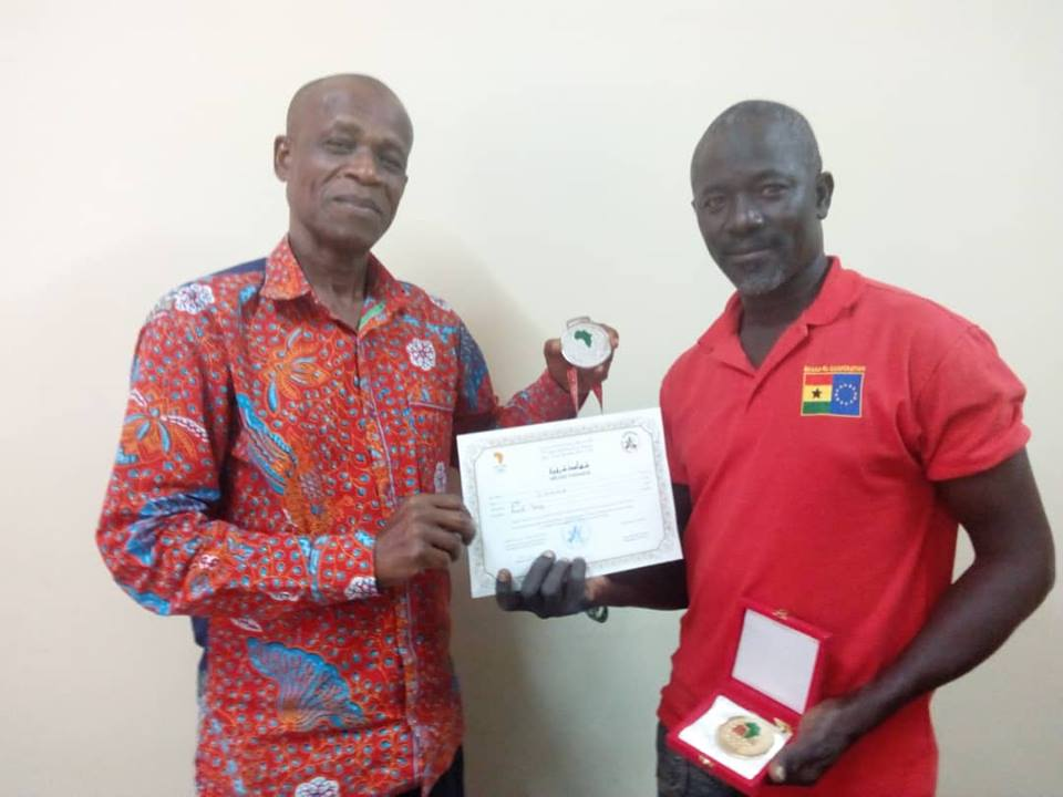 moro mumuni presents medal to paul atchoe
